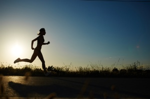 Silhouette of athletic girl running down the road to a sunset